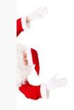 Il Babbo Natale sta osservando dalla scheda bianca Immagine Stock Libera da Diritti
