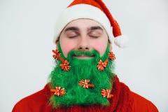Il Babbo Natale in vestiti rossi con la barba verde sorride Fotografie Stock Libere da Diritti