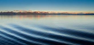 Il babordo e l'alba dell'ondulazione dell'onda di arco della nave hanno acceso le montagne nel fondo L'Alaska, U.S.A. fotografia stock libera da diritti