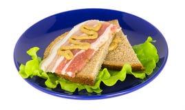 Il bacon ed il panino della senape su una foglia della lattuga si trova su un blu plat Fotografia Stock Libera da Diritti