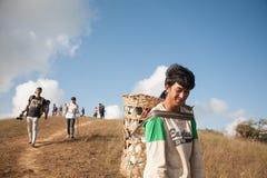 Il bagaglio di trasporto del viaggiatore del portatore sull'alta montagna Fotografia Stock