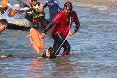 Il bagnino conserva il nuotatore Rescue in mare Immagini Stock