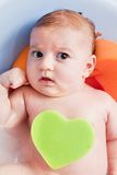 Il bagno del giovane 3 mesi di bambino con un cuore ha modellato la spugna Immagini Stock Libere da Diritti