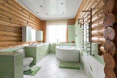 Il bagno in una cabina di ceppo rustica, nelle montagne con un bello interno casa dei ceppi del pino Immagine Stock