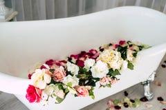 Il bagno ? in una stanza leggera decorata con i fiori ed i petali delle rose fotografie stock libere da diritti