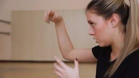 Il ballerino della ragazza dimostra i movimenti delle armi stock footage