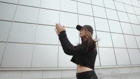 Il ballerino della ragazza in nero esegue il ballo hip-hop moderno, lo stile libero contemporaneo, ambiente urbano archivi video