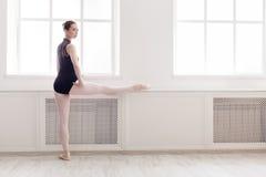 Il ballerino di balletto classico fa l'allungamento nella classe Fotografia Stock Libera da Diritti