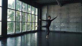 Il ballerino di balletto fa un salto in alto e una piroetta dancing del giovane contro un fondo scuro nello studio Movimento lent archivi video