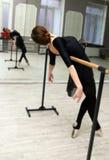 Il ballerino di balletto grazioso abbastanza giovane si scalda nella classe di balletto Immagine Stock Libera da Diritti