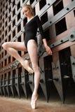 Il ballerino esile sta su una gamba vicino al vecchio portone Immagine Stock