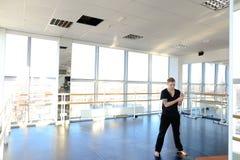 Il ballerino professionista in abiti sportivi che fanno l'allungamento si esercita dentro Immagine Stock Libera da Diritti
