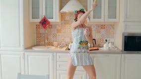 Il ballo divertente del cuoco della donna e canta con il matterello mentre cucina nella cucina a casa archivi video