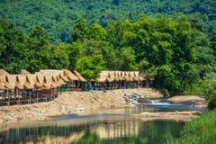 Il bambù ha fatto le baracche lungo la corrente che corre giù da Krok-e-dok Immagini Stock Libere da Diritti