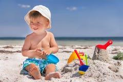 Il bambino è alla spiaggia. Immagini Stock