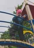 Il bambino è di 4-5 anni dietro l'inferriata del campo da giuoco Fotografia Stock Libera da Diritti