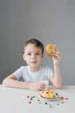 Il bambino è felice di mangiare i biscotti casalinghi con latte Immagini Stock Libere da Diritti