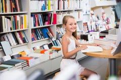 Il bambino è impegnato con un libro nella biblioteca Fotografia Stock