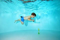 Il bambino è impegnato negli sport subacquei nello stagno Nuotate sotto acqua su un fondo blu e sugli sguardi al fondo Immagine Stock Libera da Diritti