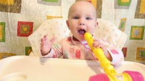 Il bambino è sedentesi e tenente un giocattolo nella sua bocca stock footage