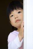 Il bambino abbastanza piccolo si leva in piedi dietro un portello Fotografie Stock