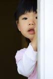Il bambino abbastanza piccolo si leva in piedi dietro un portello Immagine Stock