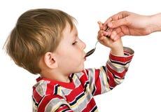 Il bambino accetta una medicina Fotografia Stock