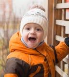 Il bambino ad un campo da giuoco nel giorno di autunno è sorpreso ed ammira, Immagine Stock Libera da Diritti