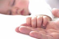 Il bambino addormentato sta tenendo la mano di suo padre immagini stock libere da diritti