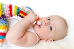 Il bambino adorabile che gioca con fatto a mano variopinto lavora all'uncinetto il giocattolo Fotografia Stock Libera da Diritti