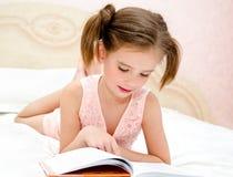 Il bambino adorabile della bambina sta leggendo un libro Immagini Stock