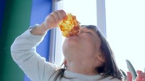 Il bambino affamato sta mangiando gli alimenti industriali nel ristorante della pizzeria alla luce solare viva stock footage