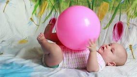 Il bambino affascinante sta trovandosi a letto e gioca con una grande palla rossa archivi video