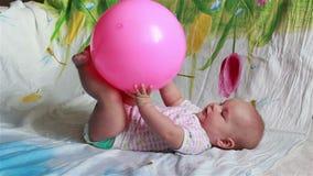 Il bambino affascinante sta trovandosi a letto e gioca con una grande palla rossa stock footage