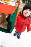 Il bambino alimenta gli uccelli nell'alimentatore nell'inverno Concetto della sorgente immagini stock