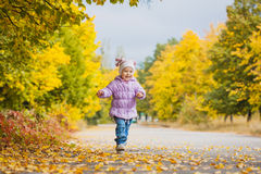 Il bambino allegro felice sta correndo nel parco di autunno Fotografia Stock