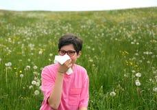 Il bambino allergico soffia il suo naso con il fazzoletto bianco Immagini Stock