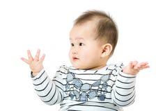 Il bambino alza sulla mano e l'esame del lato fotografie stock libere da diritti