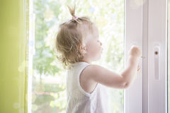 Il bambino apre la finestra con la fine della serratura su Bambino alla macro della finestra Finestra con la serratura per il ` s Fotografia Stock Libera da Diritti