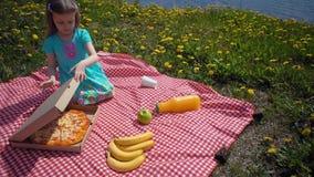 Il bambino apre la scatola di cartone con pizza sul litorale archivi video