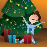 Il bambino apre un regalo vicino all'albero di Natale Fotografia Stock Libera da Diritti