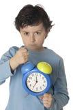 Il bambino arrabbiato vicino sveglia presto Fotografia Stock Libera da Diritti