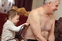 Il bambino ascolta i polmoni del nonno Immagine Stock