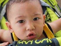 Il bambino asiatico con dubbioso considera il suo fronte Immagini Stock