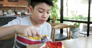 Il bambino asiatico felice gode di di mangiare il dolce insieme stock footage