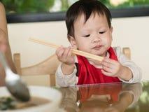Il bambino asiatico impara mangiare i bastoncini della tenuta del pasto lei stessa Immagini Stock