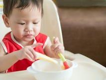 Il bambino asiatico impara mangiare il pasto lei stessa Immagine Stock