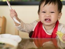Il bambino asiatico impara mangiare il pasto lei stessa Immagini Stock Libere da Diritti