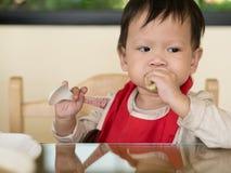Il bambino asiatico impara mangiare il pasto lei stessa Fotografie Stock Libere da Diritti