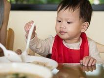 Il bambino asiatico impara mangiare il pasto lei stessa Fotografia Stock Libera da Diritti
